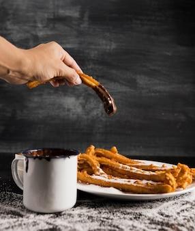 Mão segurando um churros com chocolate e uma xícara