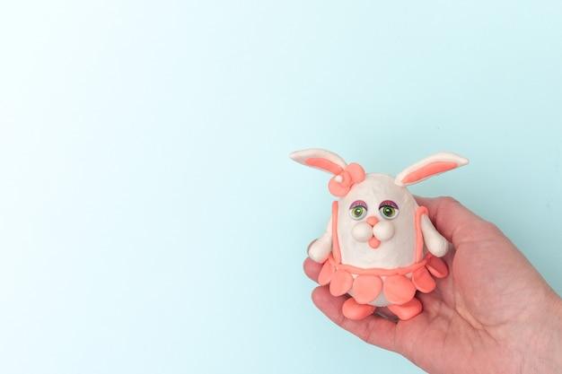 Mão segurando um coelhinho da páscoa feito de ovos e plasticina em um fundo azul