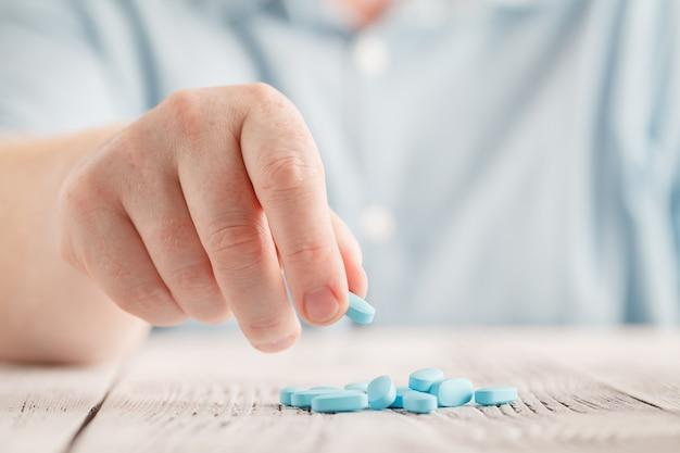 Mão segurando um comprimido azul close-up
