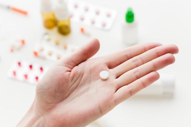 Mão segurando um comprimido de medicamento