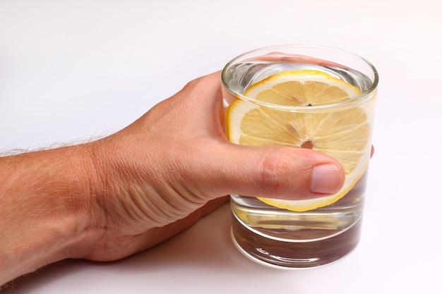 Mão segurando um copo de água com uma rodela de limão em um fundo branco