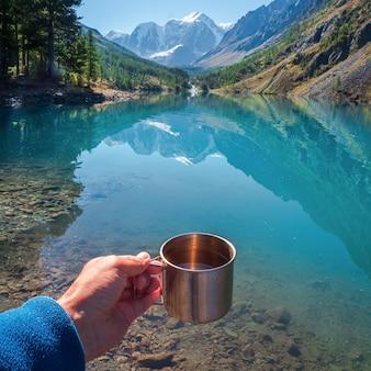 Mão segurando um copo de caminhantes com água limpa. água potável no lago azul da montanha. água potável em uma xícara de turista no contexto de um lago e montanhas nevadas.