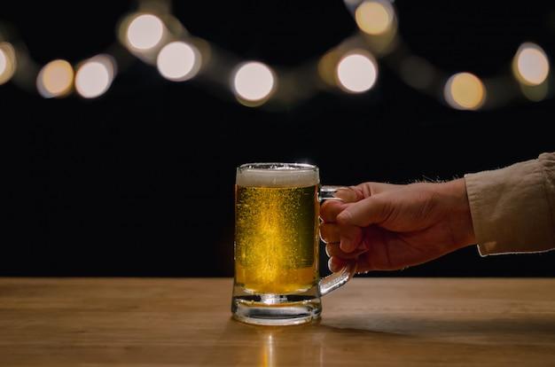 Mão segurando um copo de cerveja na mesa de madeira que tem luzes de bokeh no topo com fundo escuro.