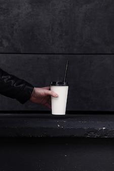 Mão segurando um copo de papel de café com bebida quente