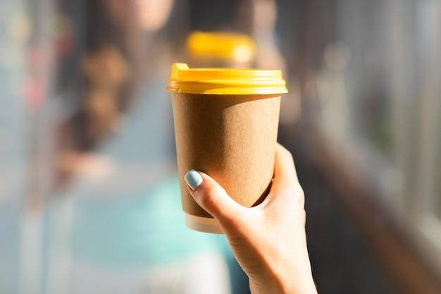 Mão segurando um copo de papel de café
