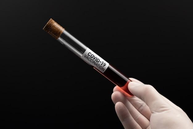Mão segurando um copo de tubo de ensaio com sangue do paciente para teste de coronavírus, isolado na mesa preta com traçado de recorte. vacina para o covid19.