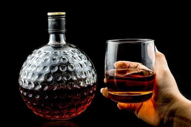Mão segurando um copo de uísque escocês premium e uma garrafa antiga