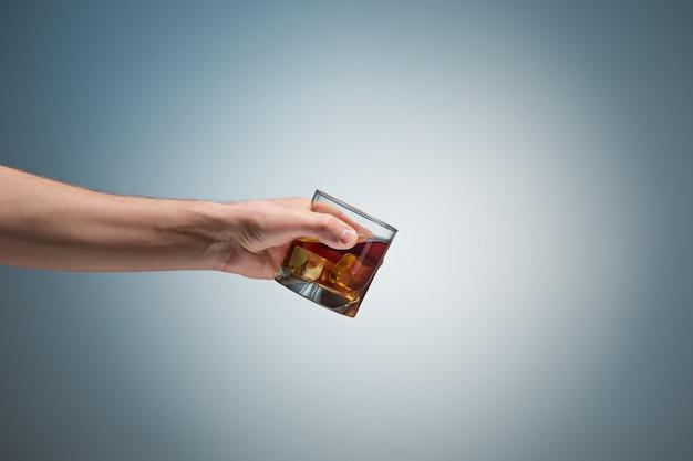 Mão segurando um copo de uísque