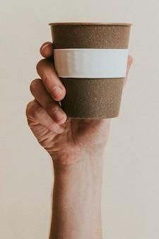 Mão segurando um copo reutilizável de cortiça