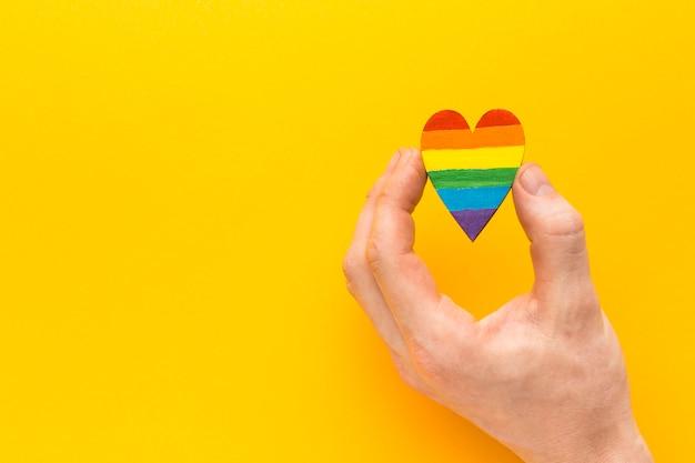 Mão segurando um coração arco-íris