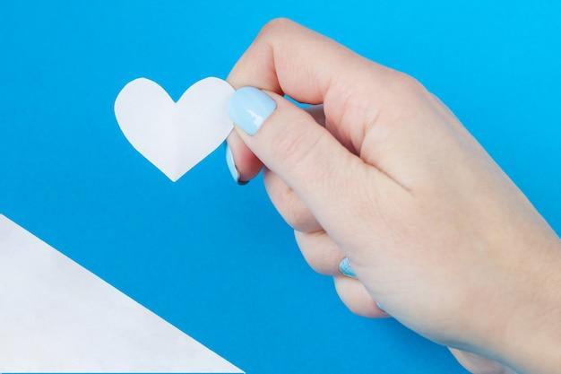 Mão segurando um coração branco sobre um fundo branco e azul