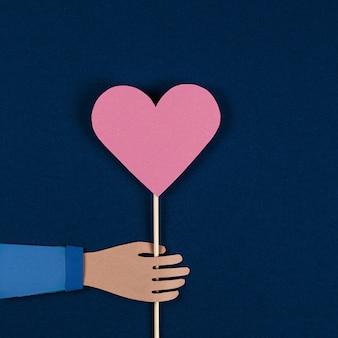 Mão segurando um coração de papel de origami. cartão de dia dos namorados, corte de papel.