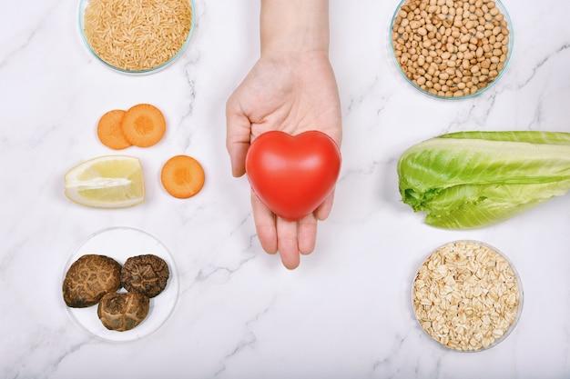 Mão segurando um coração entre diferentes alimentos