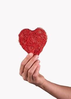 Mão segurando um coração entre os dedos conceito de dia dos namorados