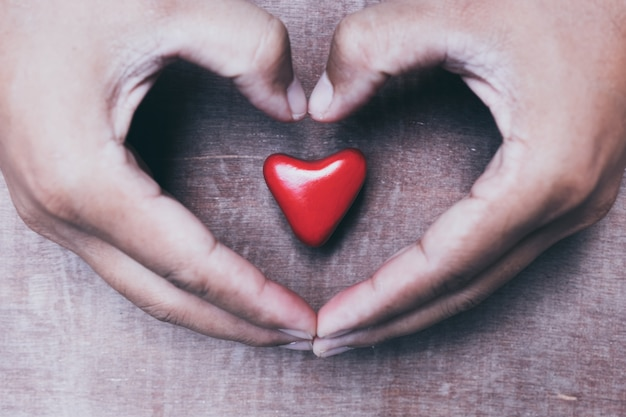 Mão segurando um coração vermelho, amor do dia dos namorados, tom vintage