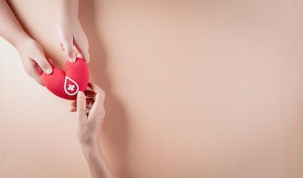 Mão segurando um coração vermelho feito à mão com uma placa ou símbolo de doação de sangue