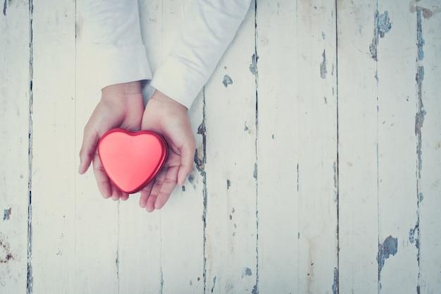 Mão segurando um coração vermelho