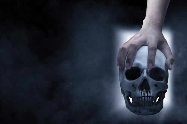 Mão segurando um crânio humano no cemitério com um fundo de porta brilhante