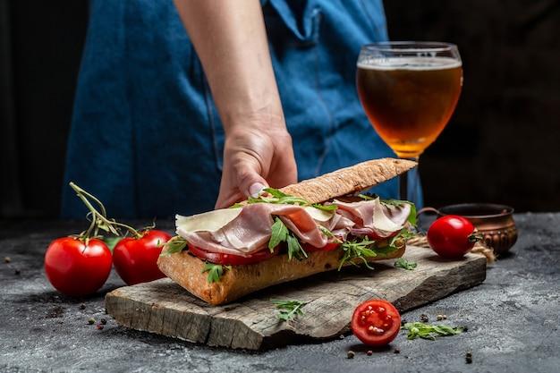 Mão segurando um delicioso sanduíche de baguete com vários vegetais maduros e presunto
