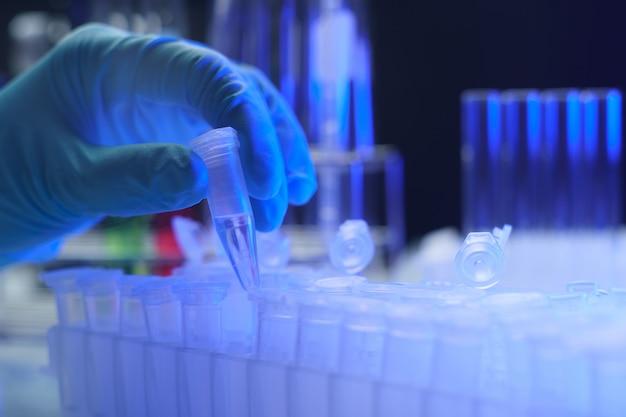 Mão segurando um dos vários tubos de ensaio em um laboratório.