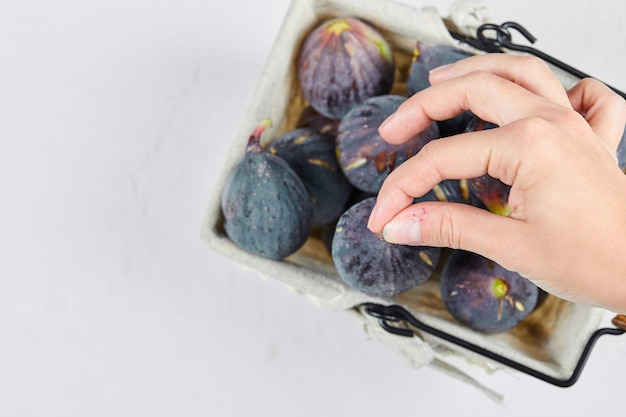 Mão segurando um figo da cesta em branco.