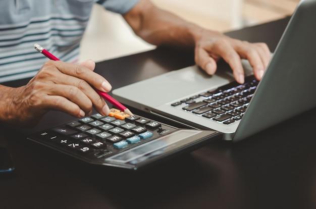 Mão segurando um lápis, calculadora e teclado de computador na mesa.