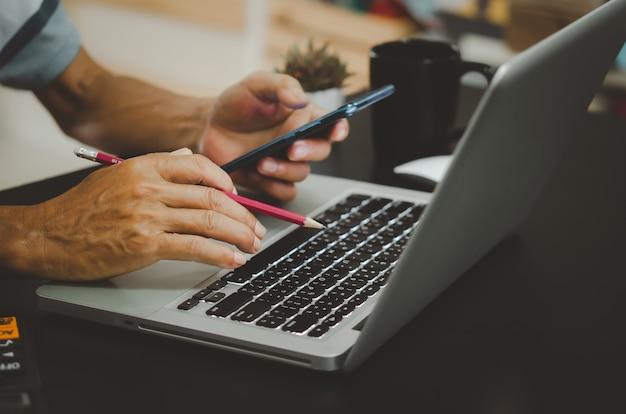 Mão segurando um lápis, calculadora e telefone celular, teclado de computador na mesa.