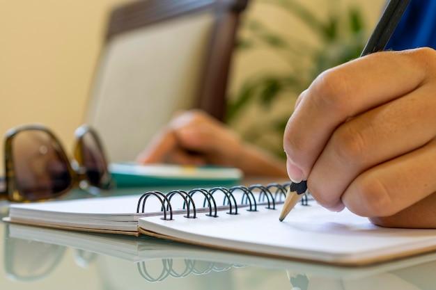 Mão segurando um lápis, fazendo anotações em um caderno espiral