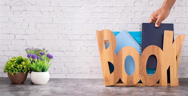 Mão segurando um livro em uma caixa de armazenamento de madeira sobre fundo de textura de parede de tijolo branco.