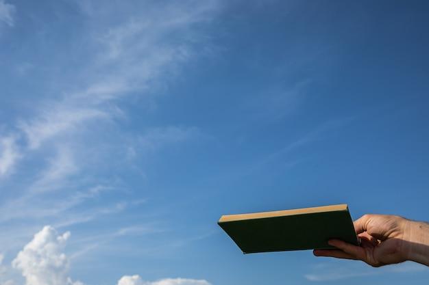 Mão segurando um livro verde até o céu azul nublado. foco seletivo.