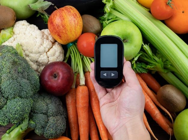 Mão segurando um medidor de glicose contra alimentos saudáveis de baixo índice glicêmico dieta para diabéticos e conceito de vida saudável