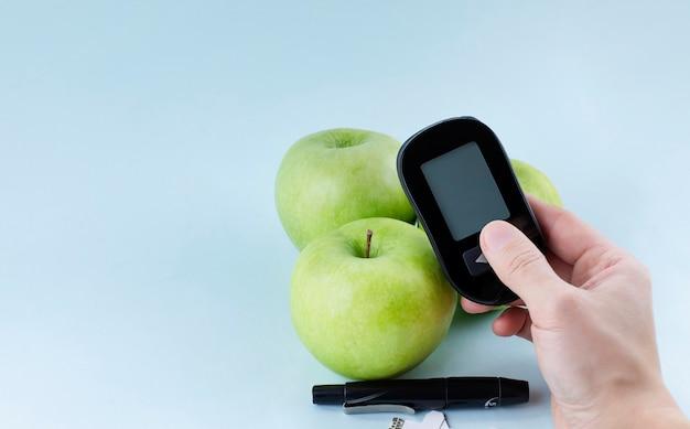 Mão segurando um medidor de glicose. dieta para diabéticos e conceito de vida saudável