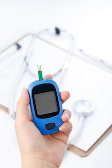Mão segurando um medidor de glicose no sangue medindo açúcar no sangue, o fundo é um estetoscópio e um arquivo de gráfico