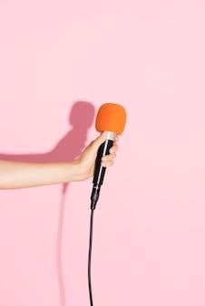 Mão segurando um microfone com parede rosa