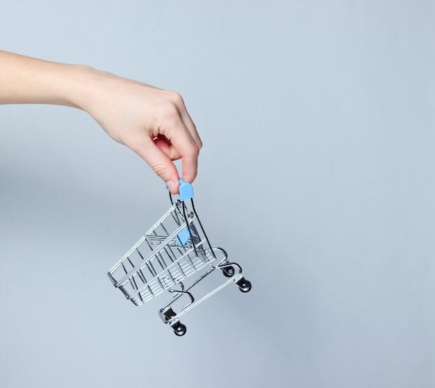 Mão segurando um mini carrinho de compras na superfície cinza