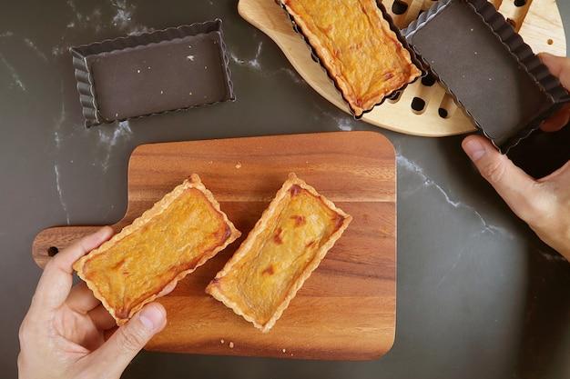 Mão segurando um molde de torta e tortinha de abóbora assada fresca colocando na tábua de pão de madeira