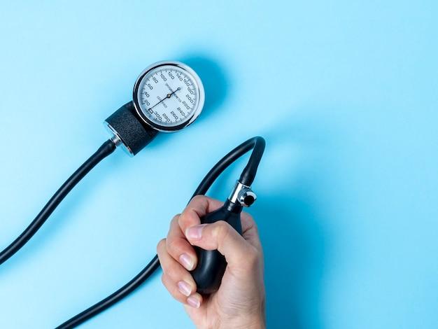 Mão segurando um monitor de pressão arterial