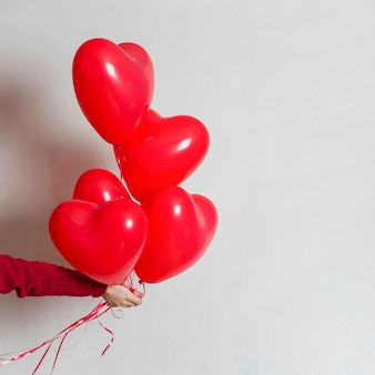 Mão segurando um monte de balões