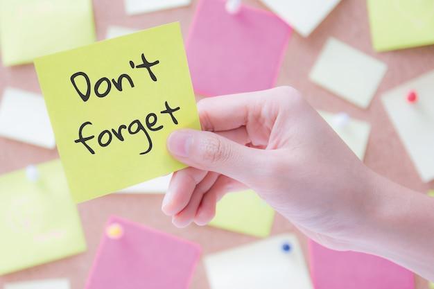 Mão segurando um papel timbrado ou postá-lo com palavras não se esqueça