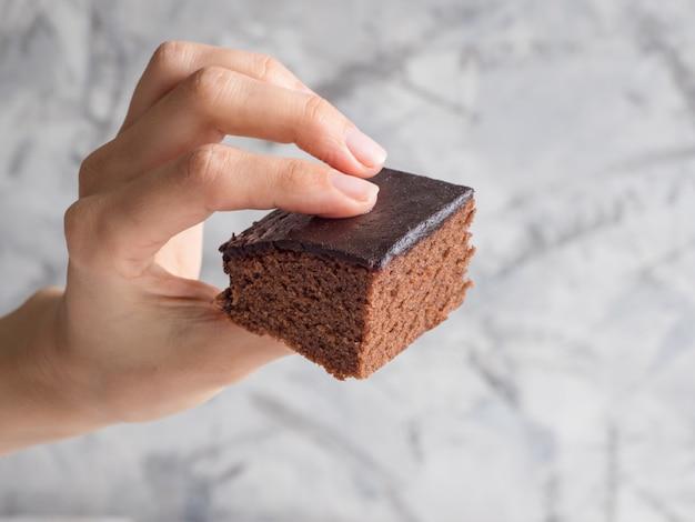 Mão segurando um pedaço de brownie recém-assados
