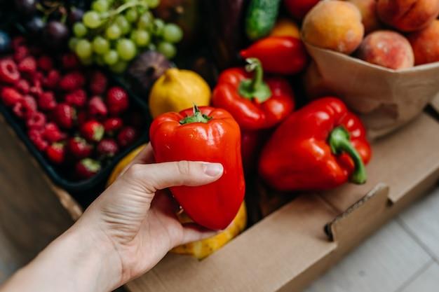 Mão segurando um pimentão vermelho em fundo de frutas e vegetais