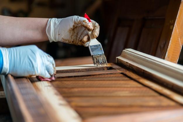 Mão segurando um pincel aplicando tinta em móveis de madeira