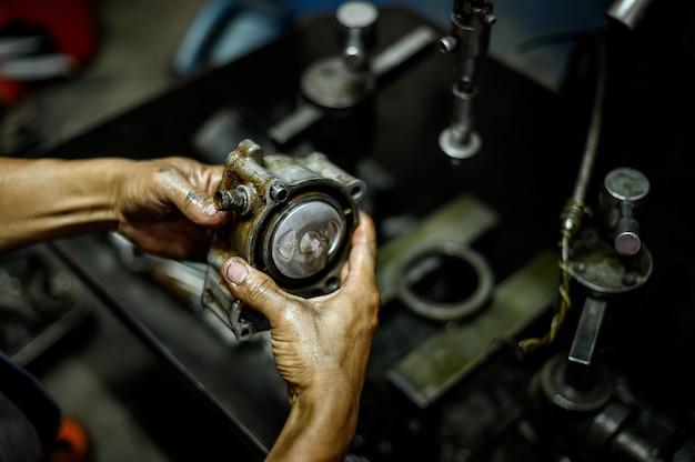 Mão segurando um pistão de motocicleta com uma máquina borrada no fundo