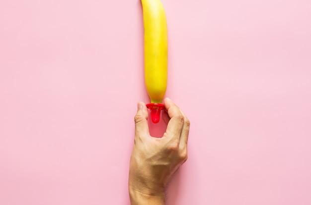 Mão segurando um preservativo para colocar uma banana para um conceito de saúde sexual mundial e dia de aids mínimo de sexo seguro