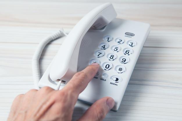 Mão segurando um receptor de telefone residencial