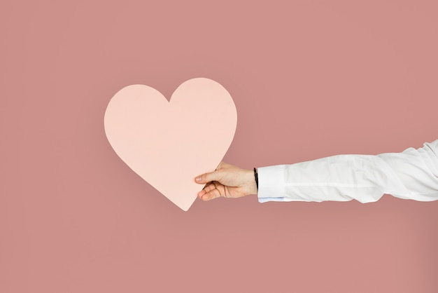Mão segurando um recorte de coração rosa, coração saudável ou conceito de amor