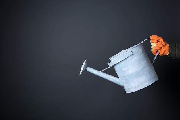 Mão segurando um regador de metal sobre uma parede cinza