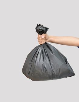Mão segurando um saco de lixo preto em um fundo cinza com traçado de recorte