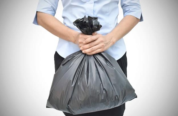 Mão segurando um saco de lixo preto sobre fundo branco com traçado de recorte