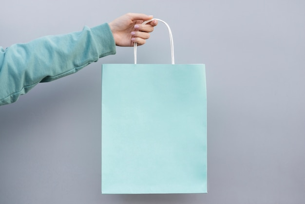 Mão segurando um saco de papel comercial